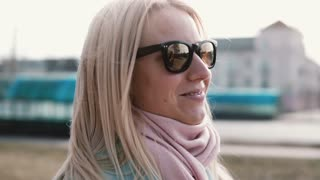 Portrait of beautiful blonde hair Caucasian woman. Happy smiling pretty young 20s girl in stylish sunglasses side view.