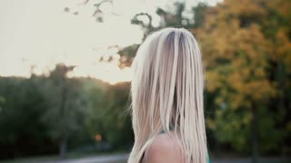 Portrait of beautiful young woman in park on sunset. Blonde girl turns and looks at camera, her hair waves. Slow motion.