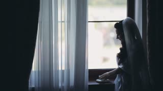 Portrait of brunette bride near the window. Woman in white elegant peignoir drinking coffee and looking into distance.