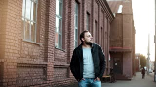 Portrait of casual handsome Caucasian man. Confident young male in leather jacket walks by camera. Red brick wall 4K.