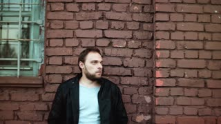 Portrait of casual handsome European man. Thoughtful young male in leather jacket touches his hair. Red brick wall 4K.