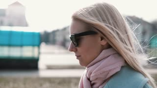 Portrait of confident Caucasian blonde girl 20s. Slow motion calm smiling young lady walking in stylish sunglasses.