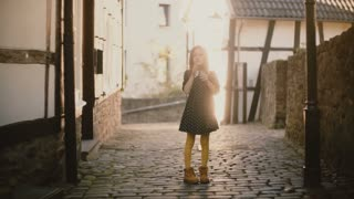 Portrait of cute Caucasian girl blowing kisses. Happy female kid posing at camera on a paved street. Sunlight flare. 4K.