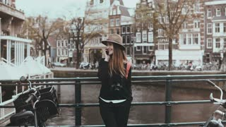 Portrait of cute European female make phone call. Zoom in. Happy to hear each other voice. Amsterdam, Netherlands. 4K.