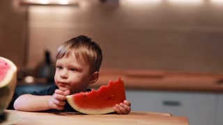 Portrait of cute little boy sitting at the table on the kitchen. Holding a piece, touching a watermelon, licks finger.