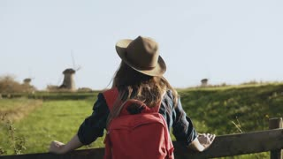 Portrait of European girl near rustic windmill. Attractive female looks around enjoying sunlight and smiling happily. 4K