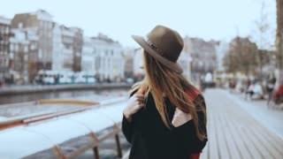 Portrait of European lady tourist walk near river. Happy thoughtful traveler female looks around on an embankment. 4K.