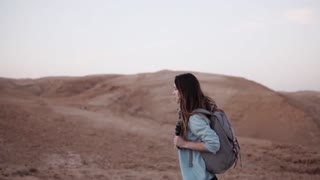 Portrait of European woman in desert. Slow motion. Young girl walks in desert canyon. Life difficulties and trials.