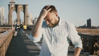 Portrait of happy Caucasian freelancer touching hair and smiling at camera. Sunrise at Brooklyn Bridge, New York City 4K