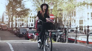 Portrait of happy Caucasian girl riding a bicycle. Slow motion. Pretty smiling 20s female on a leisure city bike ride.