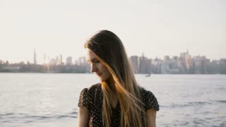 Portrait of happy European girl with flying hair posing, smiling at camera on sunset beach with New York City skyline 4K