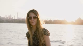 Portrait of happy young European girl in sunglasses posing, hair blowing in the wind on amazing New York sunset 4K.