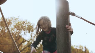 Portrait of little adorable girl on playground. Cute smiling 6 year old girl goes over obstacles on showground cheerful.