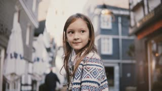 Portrait of little European girl 5-7 years old. Posing at camera smiling, amazing long hair. Old houses background. 4K.