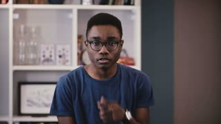 Portrait of serious African American student. Handsome thoughtful black young man adjusting glasses looking at camera 4K