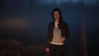 Portrait of stressed Caucasian girl near dark field. Beautiful frustrated female near foggy forest worried and shocked.