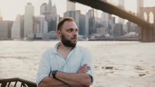 Portrait of successful European freelance businessman standing arms folded at Brooklyn Bridge New York river scenery 4K.