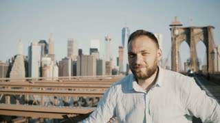 Portrait of successful happy Caucasian businessman crossing arms, smiling at camera at Brooklyn Bridge, New York City 4K