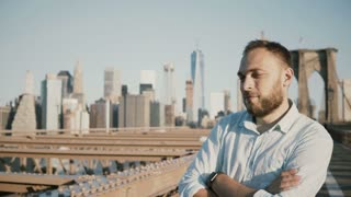 Portrait of successful happy European businessman with arms folded smiling, looking back at Brooklyn Bridge, New York 4K