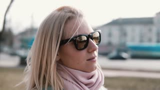 Portrait of thoughful attractive Caucasian girl. Pretty adult 30s blonde female in stylish sunglasses with flying hair.