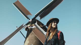 Portrait of traveller woman near old windmill. Incredible cinematic low angle. Girl in hat in front of farm mill. 4K