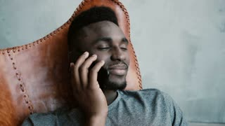 Portrait of young African male sitting in the chair and talking on Smartphone. Man laughs and nods his head agreeing.