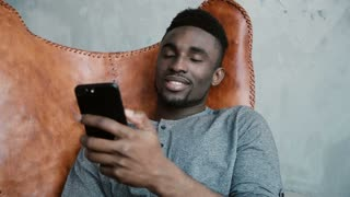 Portrait of young African man sitting in the chair, using Smartphone. A handsome male smiling and talking on the phone.