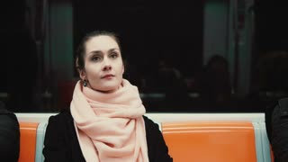 Portrait of young and thoughtful woman sitting in subway. Girl uses public transport, looking around, at window.