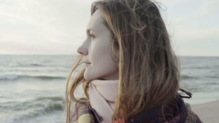 Portrait of young attractive female standing on the shore of the sea with plaid, looking into the distance and thinking.