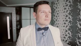 Portrait of young attractive man looking at camera and putting in order bow tie. Showman in white sit getting ready.