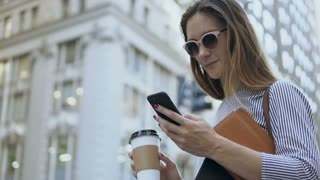 Portrait of young beautiful businesswoman in sunglasses holding the cup of coffee using the smartphone on the street.