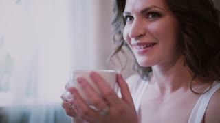 Portrait of young beautiful woman drinking coffee in bedroom. Morning of the attractive girl in home.