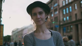 Portrait of young beautiful woman in hat standing on the street. Happy stylish female looking on camera and smiling.