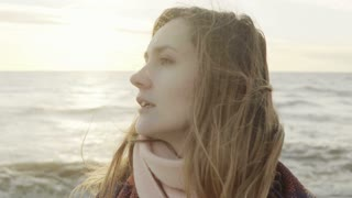 Portrait of young beautiful woman looking into the distance on the shore of sea. Female standing on beach in cold day.