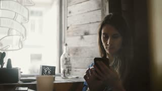 Portrait of young beautiful woman sitting in cafe near the window and using the smartphone, surfing the Internet.