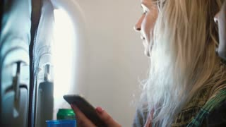 Portrait of young beautiful woman sitting near the window in plane and using the smartphone. Female and man traveling.