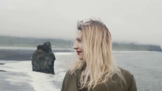 Portrait of young beautiful woman standing on black beach, near Troll toes rocks in Iceland and smile, hair wave on wind