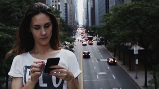 Portrait of young beautiful woman standing on the bridge in New York, America and using the smartphone.