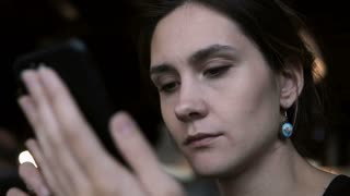 Portrait of young beautiful woman using the smartphone and talking with someone near her. Female typing the message.