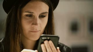 Portrait of young beautiful woman with hat in gallery and using smartphone. Student female spending leisure time alone