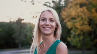 Portrait of young blonde woman standing in the park on sunset and looking at camera. Happy girl spending time outside.