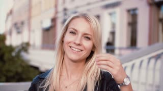 Portrait of young blonde woman standing in the street. Beautiful girl doing up hair and smiling, looking at camera.