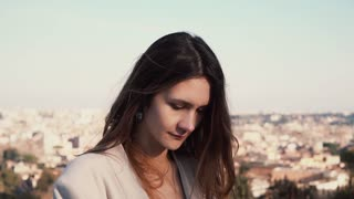Portrait of young brunette woman in Rome, Italy. Happy girl exploring the city panorama. Female looking at camera.