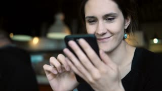 Portrait of young brunette woman sitting in cafe and using the smartphone for surfing the online Internet shops,