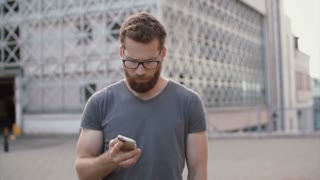 Portrait of young businessman uses smartphone for calls. Attractive man have a break outside, talks with someone.