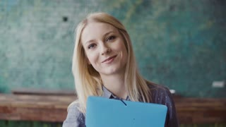 Portrait of young caucasian blonde woman looking at camera and smiling at modern office. Successful employee at work.