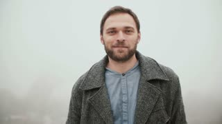 Portrait of young handsome man with beard standing against the background of Eiffel tower and looking at camera.