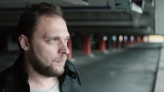 Portrait of young handsome man with beard standing on parking place alone and worried, looking around.