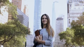 Portrait of young happy businesswoman standing in financial district of New York, near skyscrapers and holds notebooks.