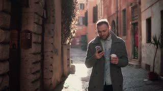 Portrait of young happy man walking in city and using smartphone. Male browse the Internet and holding cup of coffee.